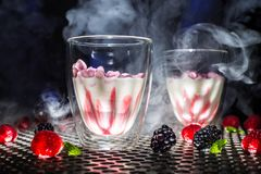 Low angle modern view dessert show or glass of red white cocktail and smoke or dry ice steam, blackberrys raspberries mint on dar stock images