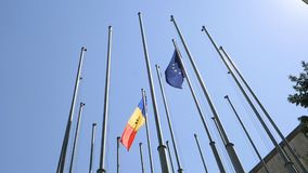 Low angle Moldova tricolour of blue, yellow, and red flag waving next to the European flag. State flag of Moldova tricolour of blue, yellow, and red waving next stock footage