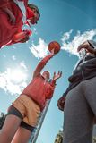 Low angle of nice young men throwing the ball. Strong throw. Low angle of nice young men throwing the ball while playing basketball royalty free stock images
