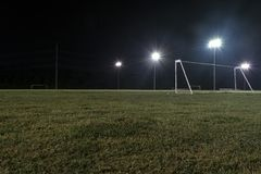 Low angle night photo of goal on empty soccer field. Low angle photo of a soccer goal without a net on an empty sports field at night with the lights on and the Stock Images
