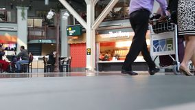 Low angle with people foot walking inside YVR airport. With blur food court background stock video footage