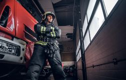 Low angle photo. Confident fireman wearing protective uniform standing next to a fire engine in a garage of a fire stock image