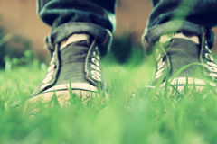 Low angle photo of green grass and person's shoes. selective focus. retro filtered.  Royalty Free Stock Photography