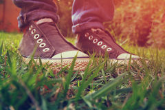 Low angle photo of green grass and person's shoes. selective focus. retro filtered.  Royalty Free Stock Photo