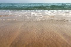 Low angle photo from ground level - beach sand wet from sea, drops of water in air, small waves and blurred ocean in distance. Ab stock images