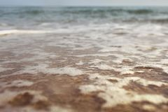 Low angle photo from ground level - beach with shallow water and white foam over sand, wet drops in air, blurred ocean in distance stock image