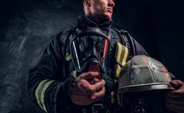 Low angle photo of a man wearing a fire suit holding an oxygen mask and helmet, looking sideways. Studio photo against a dark textured wall royalty free stock photography