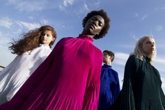 Low-angle Photography of Four Women in Assorted-color Long-sleeved Turtle-neck Dresses royalty free stock photography