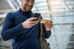 Content man purchasing airplane ticket. Low angle of pleased guy standing at the airport hall. He is using gold credit card and cellphone for paying Stock Photo
