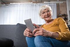 Curious smart old woman relaxing at home with mobile device stock photography