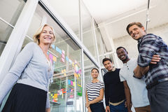 Low angle portrait of business people by plan on glass wall Stock Image