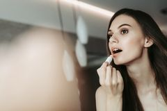 Focused girl applying makeup in the apartment stock photos