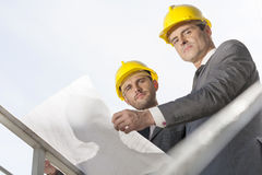 Low angle portrait of confident young businessmen holding blueprint against clear sky Stock Photo