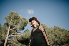 Young blonde woman walking in nature with black sunglasses and clothes and a hat. Low angle portrait of cute smiling blonde woman exploring in nature with Royalty Free Stock Photos