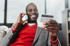 Pleased male with bankcard talking by smartphone. Low angle portrait of delighted man chatting by mobile phone at home. Focus on hand holding credit card Stock Photos