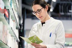Low-angle portrait of female pharmacist checking the medical pre royalty free stock photo
