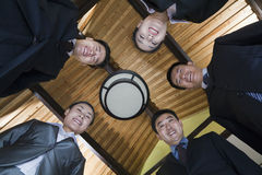 Low Angle Portrait of a Group of Businesspeople Smiling in a Circle Stock Images