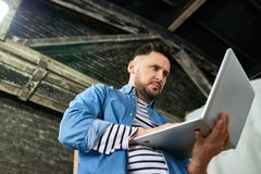 Handsome mature man using laptop. Low angle portrait of handsome mature  man using laptop while standing in barn-like workshop, copy space Royalty Free Stock Photography