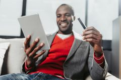 Enjoyed male person resting with tablet and bankcard in hands. Low angle portrait of happy african man sitting on couch and holding gadget and payment card Stock Image