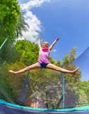 Girl acrobat split jumping on outdoor trampoline royalty free stock photography