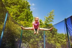 Happy girl performing split jump on the trampoline. Low-angle portrait of preteen girl performing a split jump in the air, exercising on the trampoline outdoors royalty free stock photo