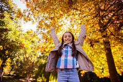 Low angle portrait of smiling girl with arms raised while standing at park Royalty Free Stock Photography