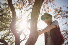 Low angle portrait of smiling man standing on tree Royalty Free Stock Photos