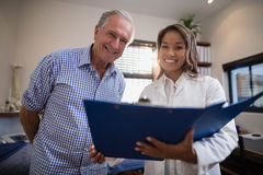 Low angle portrait of smiling senior male patient and female doctor with file Royalty Free Stock Photos