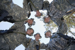 Low Angle Portrait Of Soldiers Huddling Stock Photo