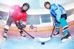 Hockey players challenging for puck on ice rink. Low angle portrait of teenage boys, hockey players, challenging for the puck on ice rink stock image