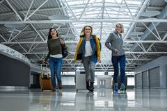 Amused friends hurrying up on the plane. Low angle portrait of three ladies with luggage running across terminal hall. They having joyful facial expressions royalty free stock photo