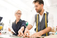 Atelier Manager. Low angle portrait of two fashion designers making clothes while standing at table in atelier workshop, copy space stock images