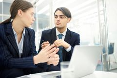 Young Entrepreneurs Collaborating. Low angle portrait of two young business people using laptop in office while collaborating on startup project, copy space stock image