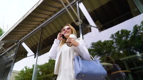 Low angle of pretty business woman talking on smartphone on coffee break outside. Low angle shot of pretty business woman talking on smartphone on coffee break stock video