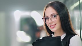 Low angle pretty successful businesswoman putting on glasses enjoying break standing in office. Medium close-up portrait smiling European female teamleader or stock video footage