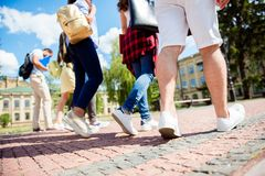 Low angle rear view shot of six student`s feet, they are walking. Outside in the park near te college building, sunny summer day, friends are enjoying their royalty free stock images