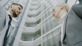 Low angle shot of bearded businessman shaking hands and talking with female business colleague in suit in hall of modern. Office building indoors stock footage