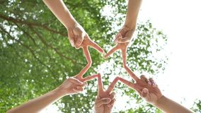 Low angle shot from below of a group of 5 young people place their hands together over sky and trees in the center of a circle. Connection people together stock video footage