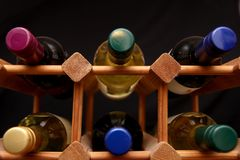 Low angle shot of bottles in a wooden wine rack on dark backgrou. Nd Stock Image