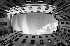 Low angle shot of building with windows and cloudy sky background. Courtyard city fisheye up view. black and white. Courtyard city look up with fisheye lens Stock Photography