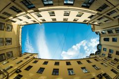 Low angle shot of building with windows and cloudy sky background. Courtyard city fisheye up view. Courtyard city look up with fisheye lens effect. Low angle Royalty Free Stock Photos