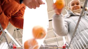 Low angle shot guy holds bag girl puts large oranges. Low angle shot close view guy holds plastic bag pretty girl puts large yellow oranges into polybag in stock video footage