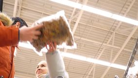 Low angle shot couple discuss whether to buy new package. Low angle shot closeup couple stands at stack discussing whether to buy new package of biscuits girl stock video footage
