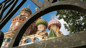 St Basil`s Cathedral in Moscow. Low angle shot of colorful domes and other fragments of St Basil`s Cathedral on Red Square near Kremlin through iron fence. It`s stock video footage