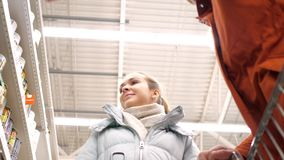 Low angle shot couple walks past shelves guy takes can. Low angle shot guy and girl walk along supermarket shelves with tinned food and man takes can stock video