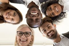 Low angle shot of excited work employees standing in circle. Low angle shot of smiling diverse office employee looking at camera hugging happy with career choice stock images