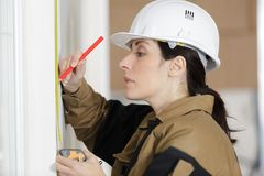 Low angle shot female carpenter working with spirit level Royalty Free Stock Image