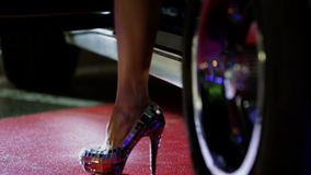 Low angle shot of female fashion model stepping out of the car. Woman in high heels is leaving the blue Corvette