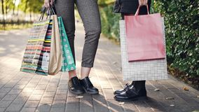 Low angle shot of female legs standing on sidewalk holding shopping bags after happy busy day in shops and malls. People stock video footage
