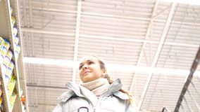 Low angle shot girl with cart walks past shelf guy appears. Low angle shot closeup pretty girl pushing shopping cart walks along shelves with tinned food guy stock video footage